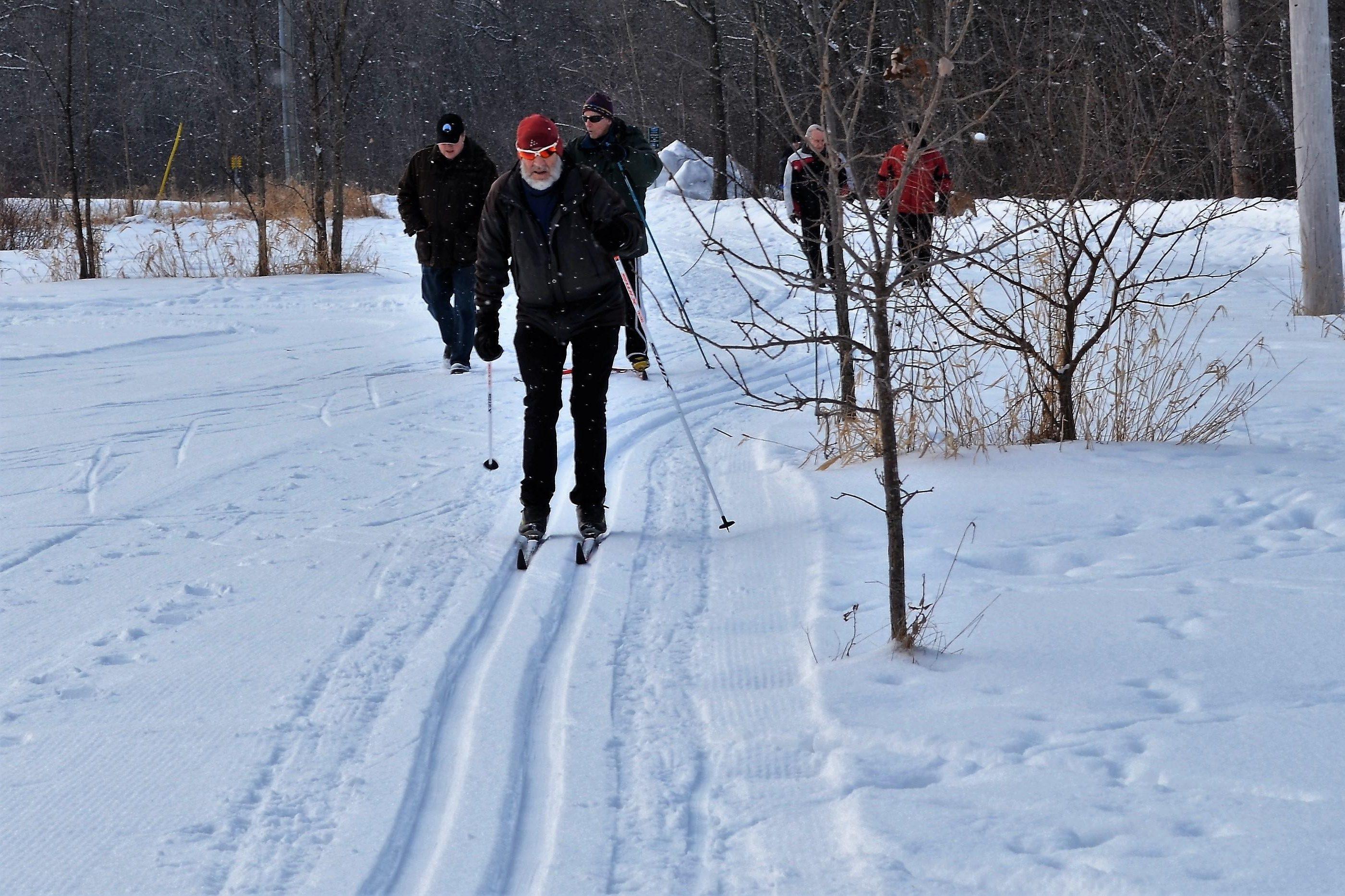 Des skieurs et des marcheurs partageant le sentier d'hiver Ski Héritage Est.