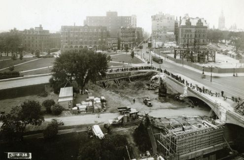 View of Connaught Place construction site and widening of the Plaza Bridge arch, with Elgin and Wellington streets in the background. August 31, 1938. Credit: Library and Archives Canada / E999909167-u