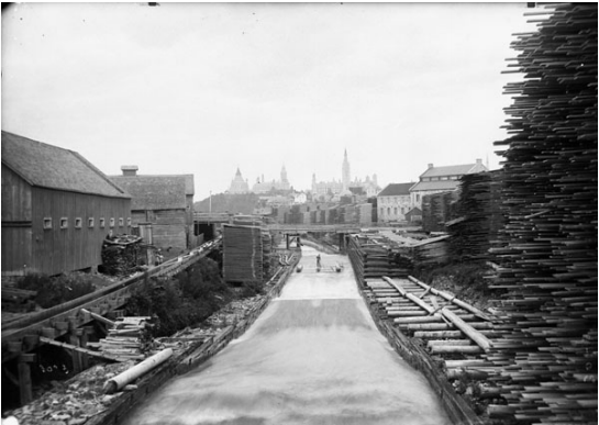 Black and white historical photo with timber frame structures shown along the south side of Victoria Island
