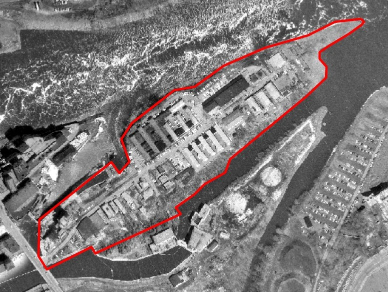 Black and white aerial view of the island, with the edges of the island indicated by a red line.