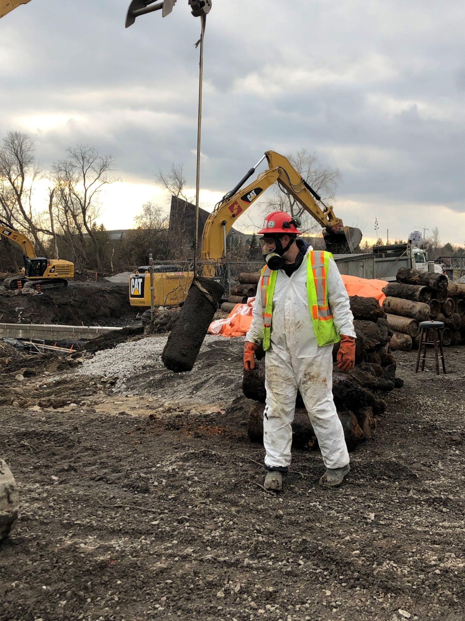 A worker geared up in a carbon-lined suit and full-face respirator stands in front of a pile of acetylene gas cylinders. In the background, there are mechanical excavators.