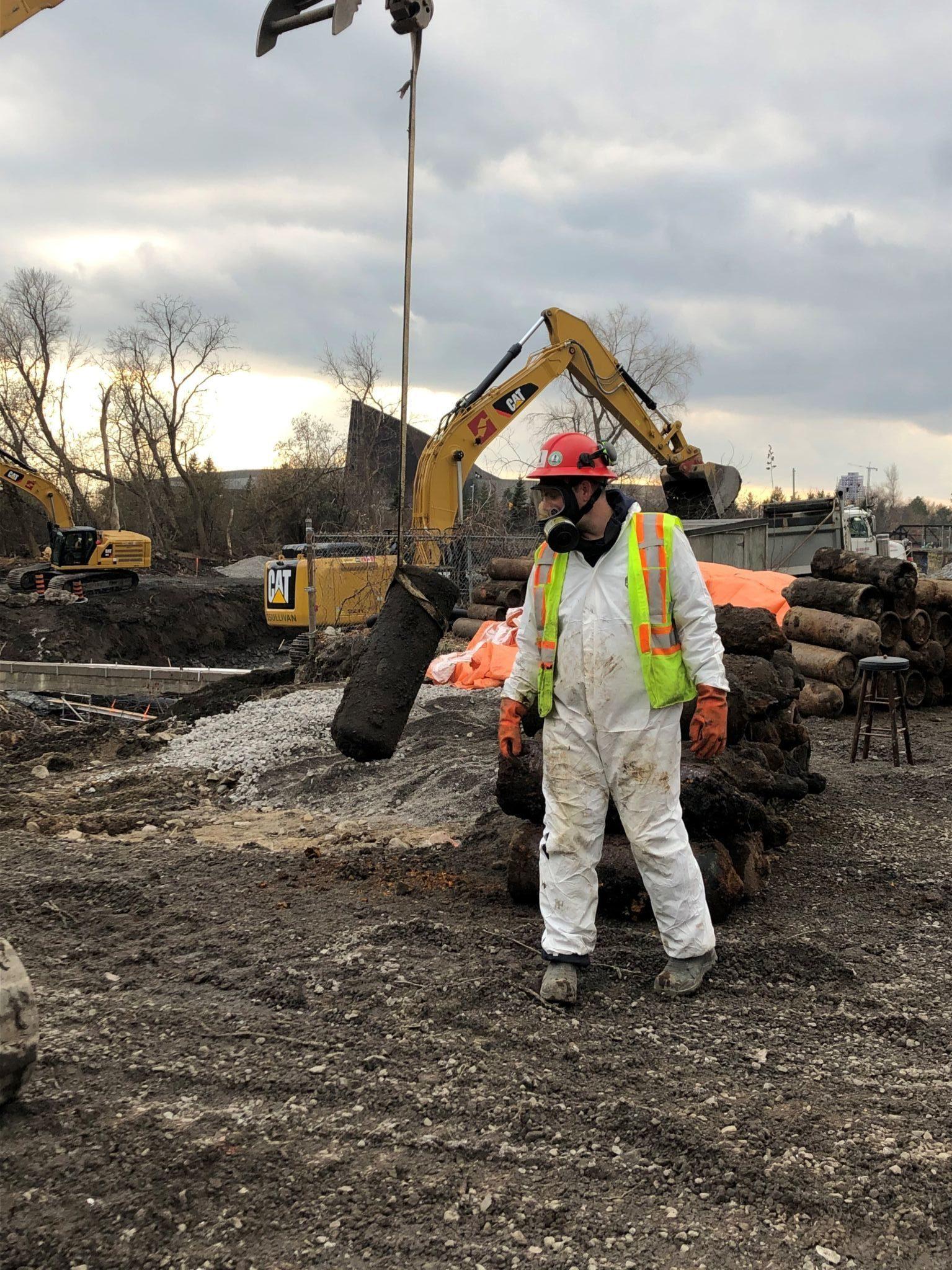 Travailleur équipé d'une combinaison en fibre de carbone et d'un masque respiratoire intégral devant une pile de bouteilles d'acétylène. En arrière-plan, des excavateurs mécaniques.