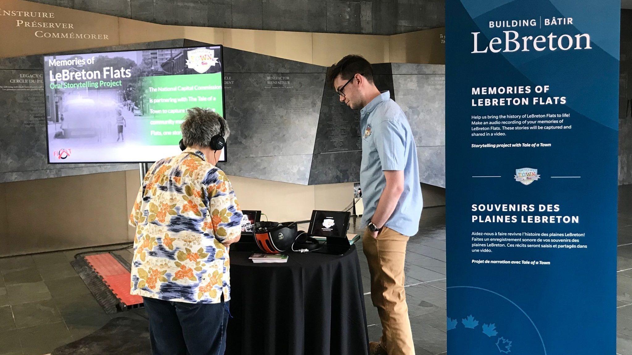 Une personne portant un casque d'écoute, vue de dos, dans une cabine d'enregistrement installée dans le cadre du projet de narration Souvenirs des plaines LeBreton. Un employé lui tient compagnie.