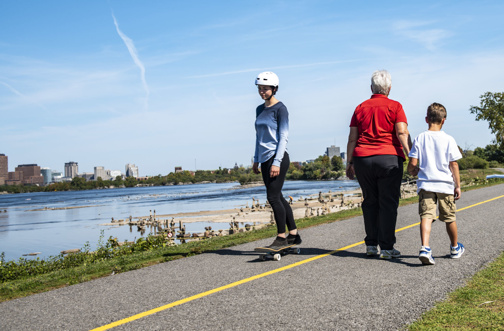 A skateboarder and two pedestrians on the pathway.