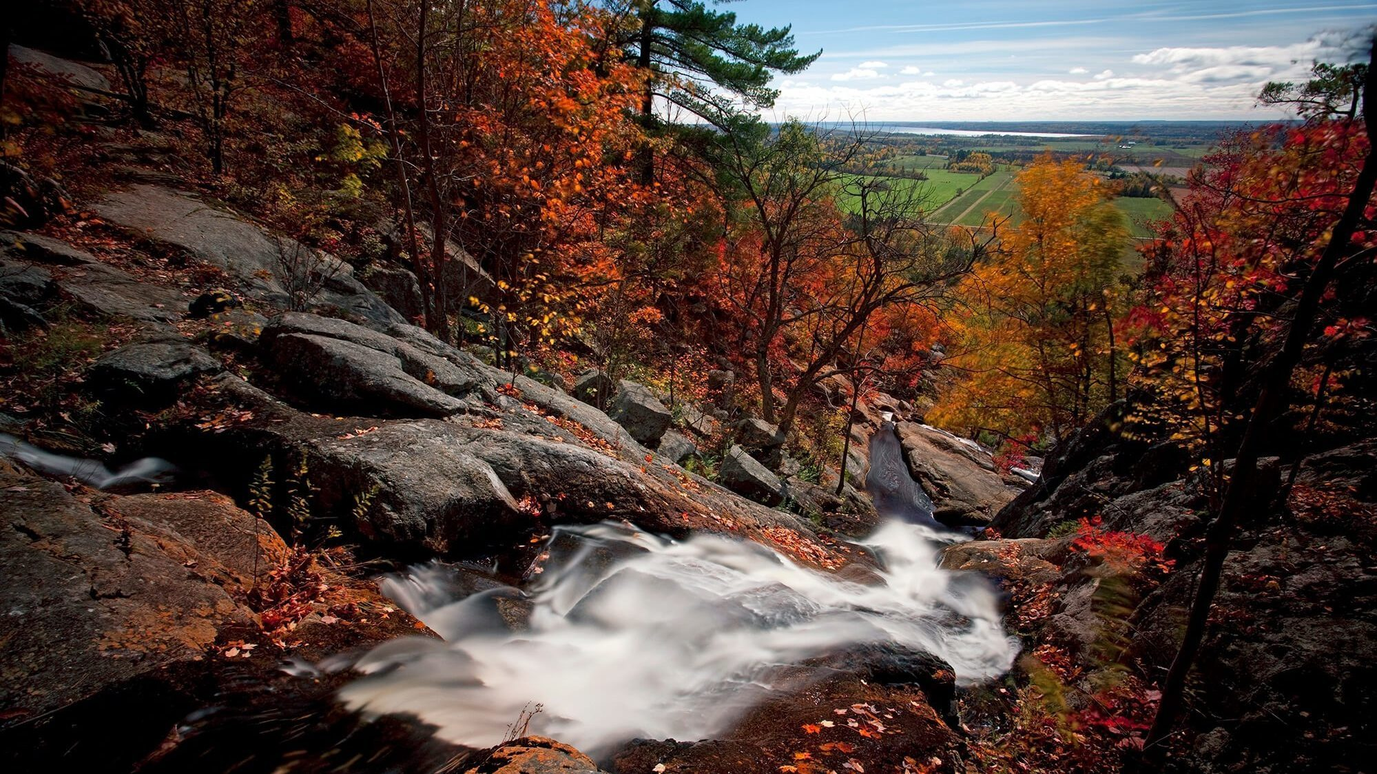 Luskville Falls in the fall, with red and orange foliage and fields in the background.