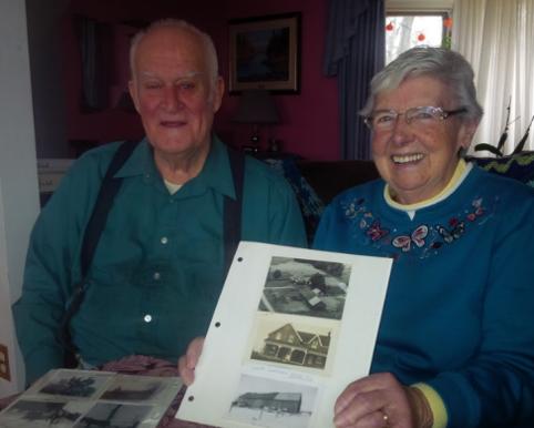 Deux aînés, tout sourire, montrant leurs vieilles photos de famille.