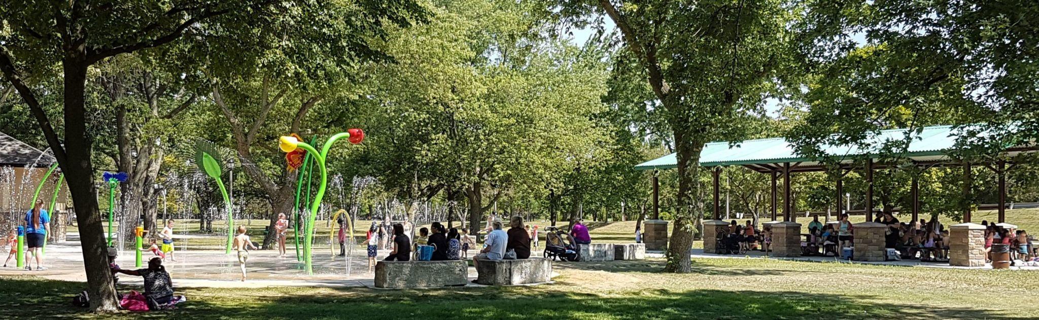 Un parc avec des arbres, des abris offrant de l'ombre et une aire de jeux d'eau, à Windsor. Source : Ressources naturelles Canada