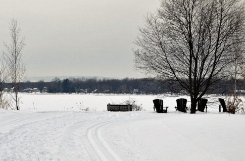 Adirondacks chairs facing the river along the Ski Heritage East winter trail.