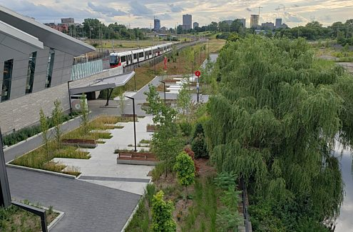 A westward view of the plaza outside of the Pimisi O-Train station, which features seating areas, landscaping and bike racks. Segment 1 of the proposed LeBreton Flats pathway will continue west from the end of this plaza.