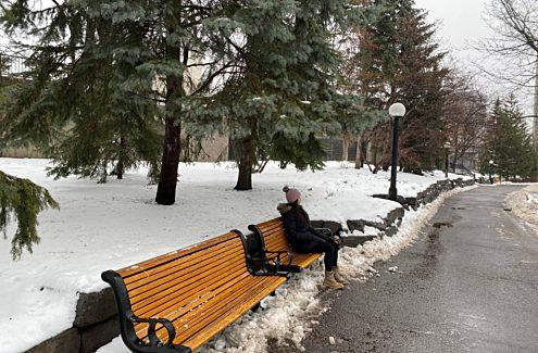 Une personne assise sur un banc de parc en hiver.