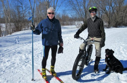 A skier, a snow biker and a dog, sharing the Ski Heritage East winter trail.
