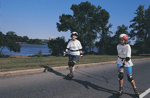 Personnes faisant du patin à roues alignées sur une promenade sans auto et fermée à la circulation automobile pendant les vélos-dimanches/vélos-weekends