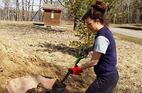 Scientifique creusant dans le sol avec une pelle.