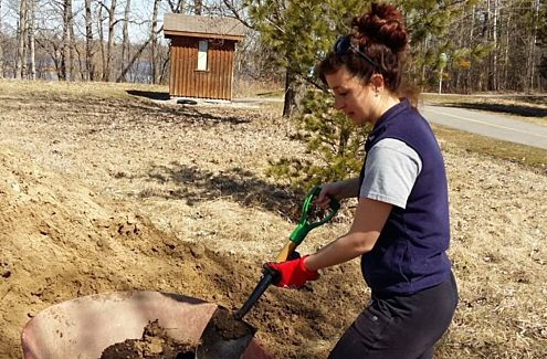 Scientist digging through soil with a shovel.