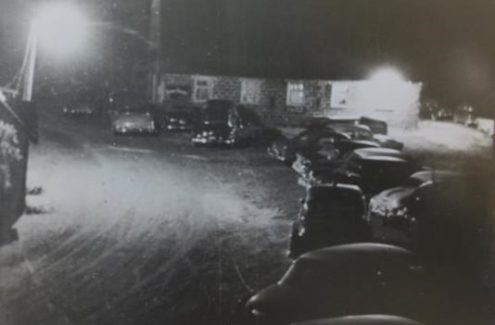 A black and white picture of cars parked outside the new Gray barn on dance night. Every Saturday night in the 1940s and 1950s, the hayloft hosted the famous Gray family barn dances.