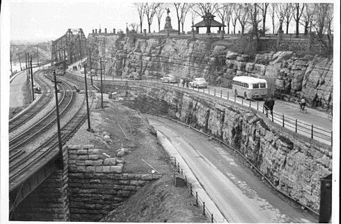 Vue du pont Alexandra et de la pointe Nepean, avec une statue et un belvédère ; voies ferrées à côté des écluses du canal Rideau, avec un bus allant d'Ottawa à Hull, années 1950. Crédit : Ville d'Ottawa