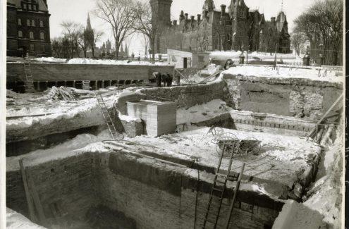Vue du chantier de construction du Monument commémoratif de guerre du Canada; au deuxième plan, des ouvriers travaillent à des pièces de bois, et à l'arrière-plan, l'édifice de l'Est. 4 février 1939. Source : Bibliothèque et Archives Canada (e999909127-u)