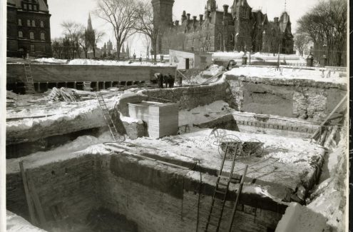 View of the National War Memorial construction site; large square pits, and builders working with lumber, in the middle ground; the East Block is in the background, February 4, 1939. Source: Library and Archives Canada (e999909127-u)