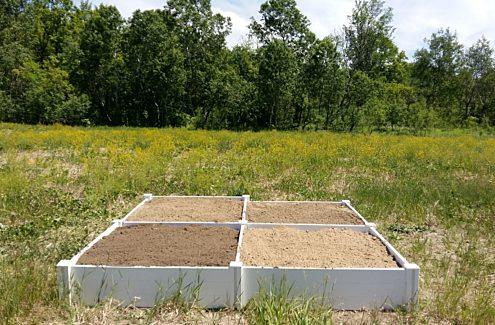 Quatre bacs à fleurs remplis de divers types de sol.