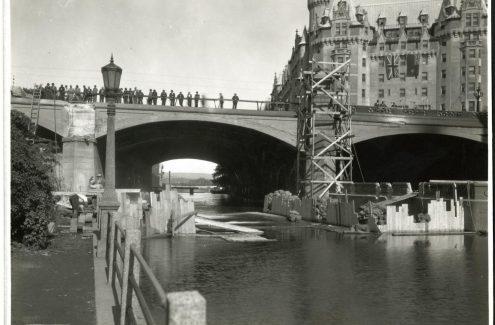 Des badauds observent l'élargissement du pont Plaza, et à l'arrière-plan, le Château Laurier. 25 août 1938. Source : Bibliothèque et Archives Canada (e999909164-u)