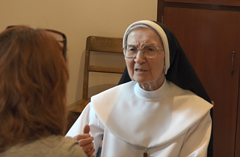 Sœur Marie-Jeanne-du-Lys, wearing a religious habit, giving an interview to Marie Roy, who is seen from behind.
