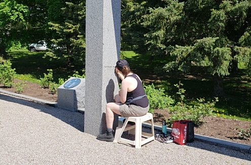 Contractor hand-painting letters on a stone monument.