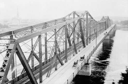 A historical image of Alexandra Bridge that features horse-drawn carriages crossing along the East side of the bridge, circa 1900. Credit: LAC/Topley/PA-009430