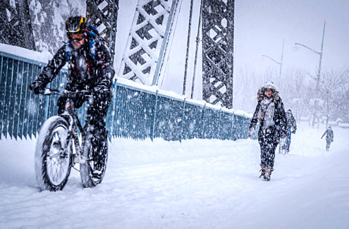 Cyclists and pedestrians on the Alexandra Bridge walkway on a snowy day. Credit: NCC