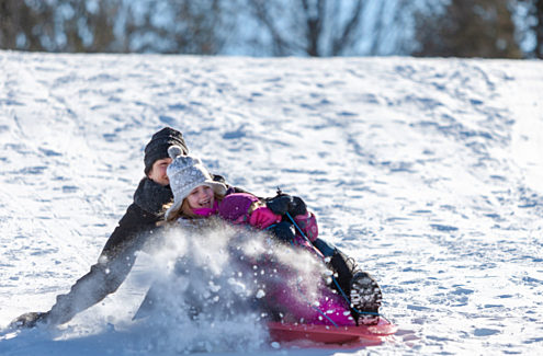 Adult and child tobogganing