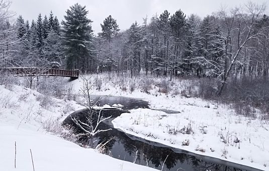 A stream running through a snowy landscape near the Gatineau Park Visitor Centre.