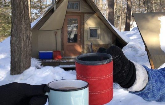 Two people raising their cups in front of a four-season tent in winter.