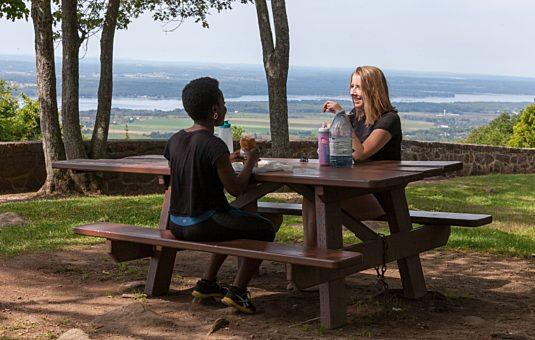 Deux personnes assises à une table de piquenique au belvédère Étienne-Brûlé.