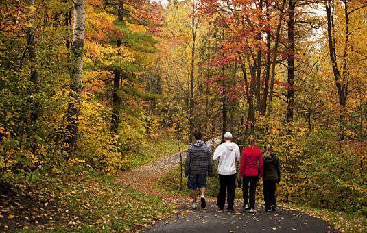 People walking on a trail in the Greenbelt in the fall
