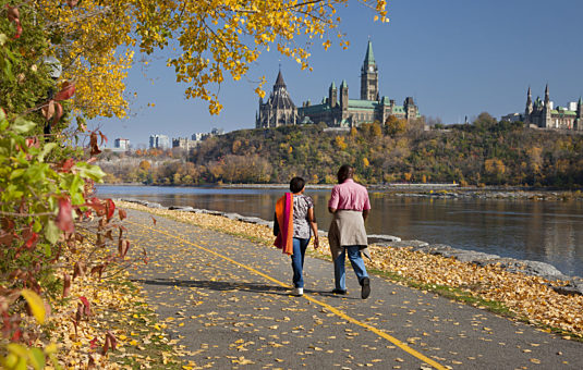Two people walking along a multi-use pathway by the Ottawa River. There are leaves on the ground, and Parliament Hill is in the background.