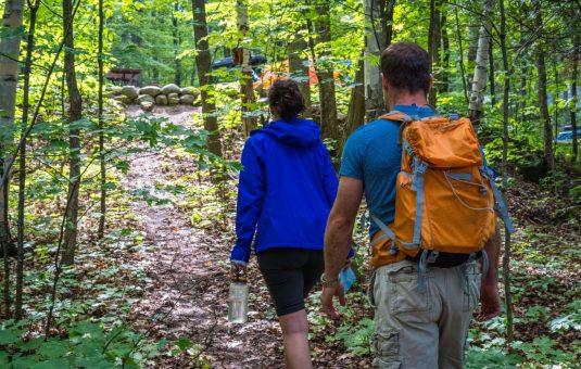 2 people walking on a trail