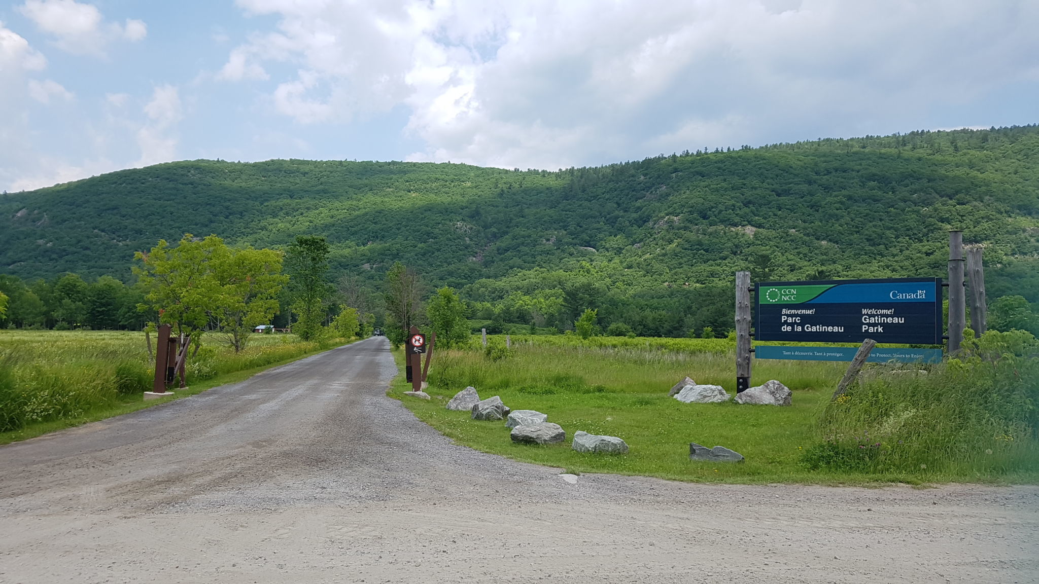 The Luskville Falls area in summer. Welcome sign and gravel road in the foreground. The hills of the Outaouais in the background.