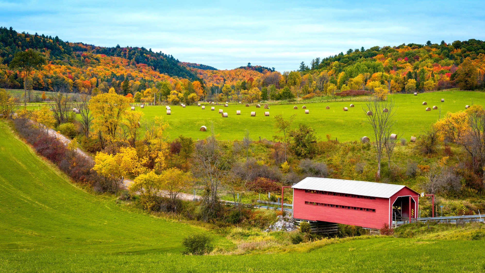 View of Meech Creek Valley in the fall. Scene of a covered bridge and haybales, with ochre- and orange-coloured trees in the background.