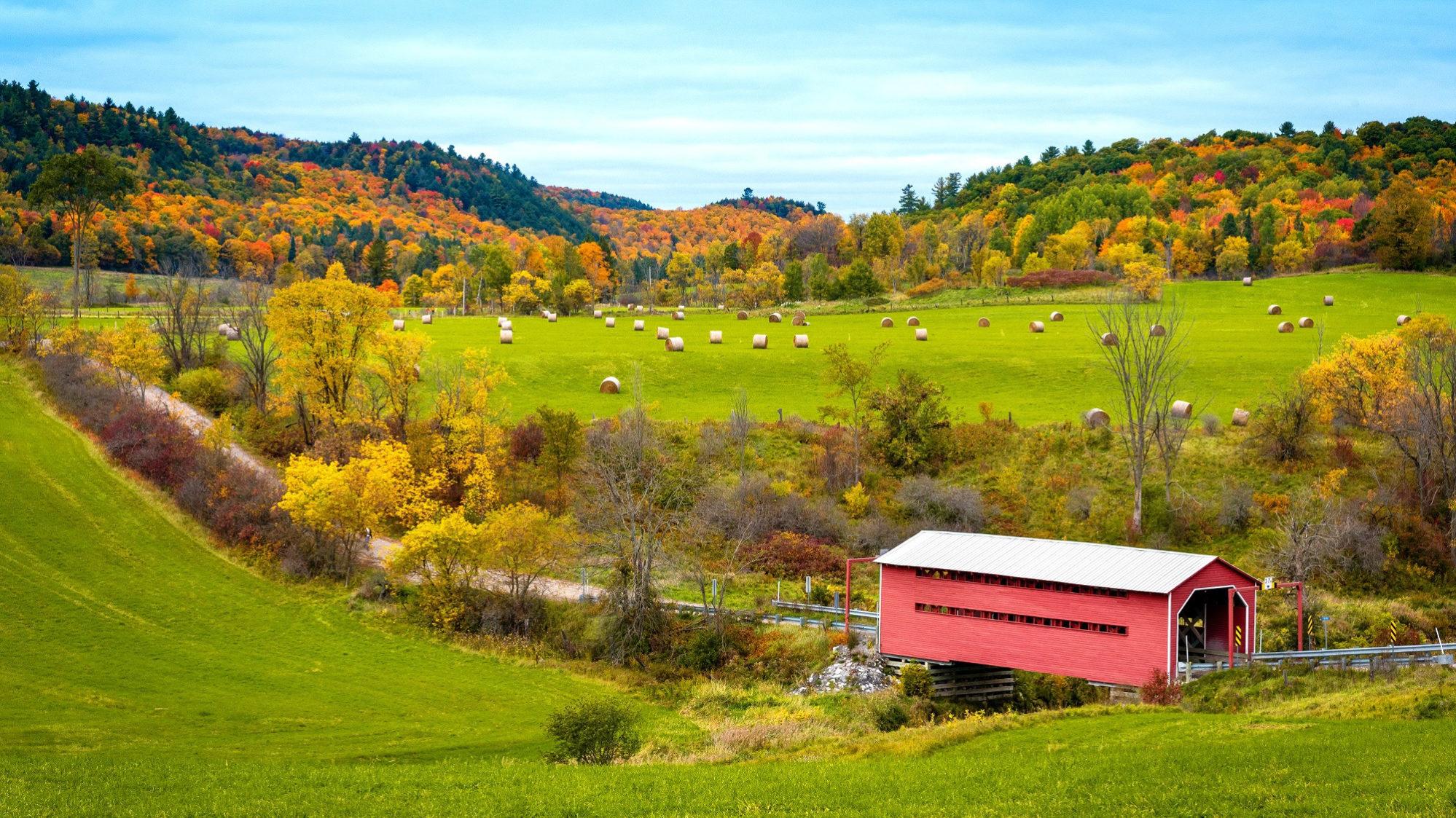 Vue de la vallée du ruisseau Meech en automne. On y voit un pont couvert, des meules de foin et des arbres au feuillage ocre et orangé en arrière-plan.
