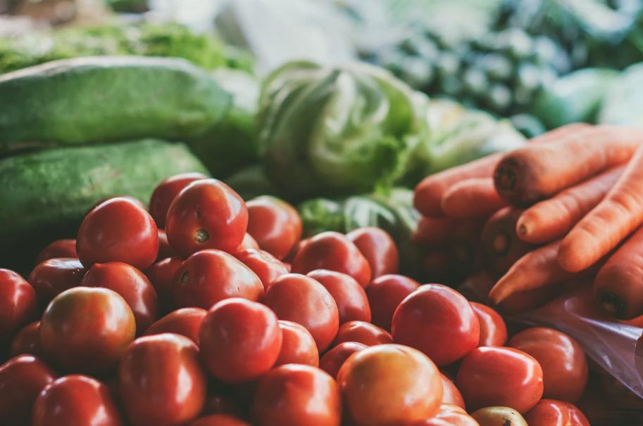 Plan rapproché d'un étal de tomates, carottes et divers légumes verts